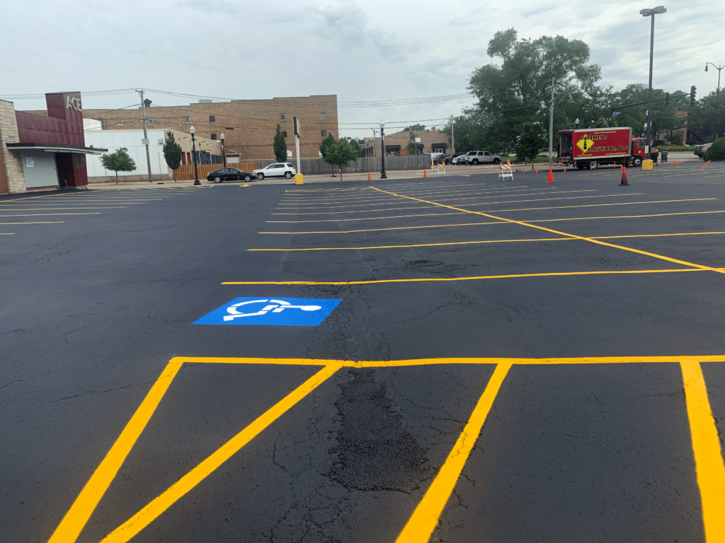 Asphalt pavement repairs of sealcoat and striping at Ace Hardware.