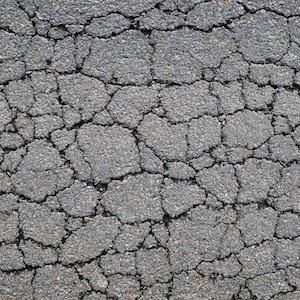 Severe alligator crack patterns on an asphalt pavement surface.
