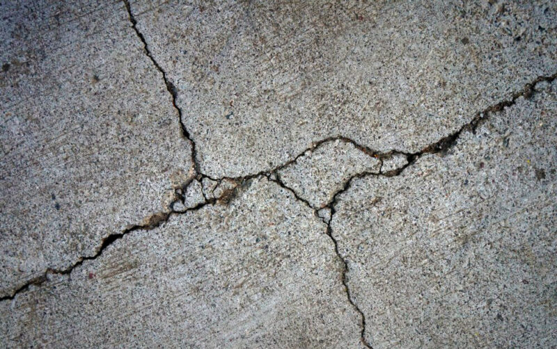Cracked driveway in need of major asphalt or concrete pavement repairs.