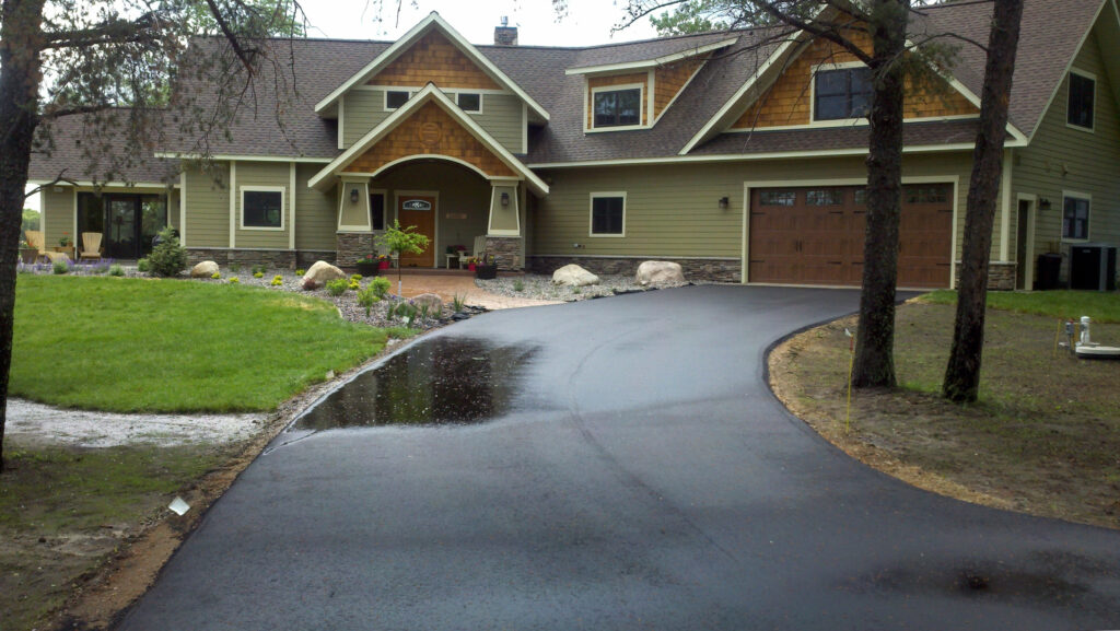 Asphalt driveway with puddles forming, showing issues with the drainage system in place.